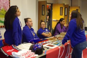 The raffle table for the powwow containing the prizes you could win in the raffle with the staff in purple seated behind it.