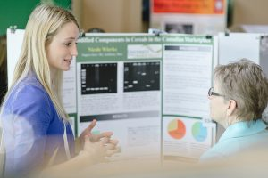 Blond student presenting work to another woman
