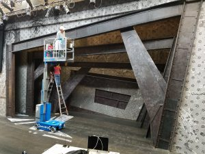 The Machinal Set being built, large metalic beems framing the stage, very indurstiral looking