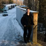 Picture of Robin Nave standing against a fence in the city of Anchorage.