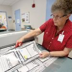 A picture of Jeanne Bridges cutting out templates for a project.