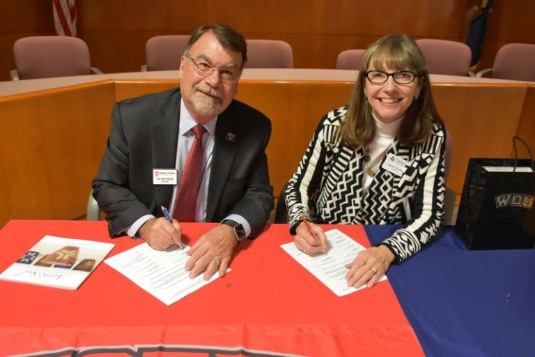 Western Oregon University President Rex Fuller (left) and Clackamas Community College President Joanne Truesdell signing a dual enrollment agreement