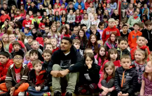 Tyrell sitting on the ground surrounded by Turner Elementary students