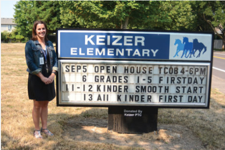 Christine Bowlby standing in front of the Keizer Elementary sign.