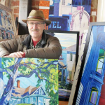 Photo of Gary Allen posing with one of his paintings.