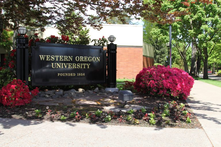 Western Oregon University campus sign with flowers around it