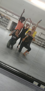 A selfie in a mirror of a group of five people waving