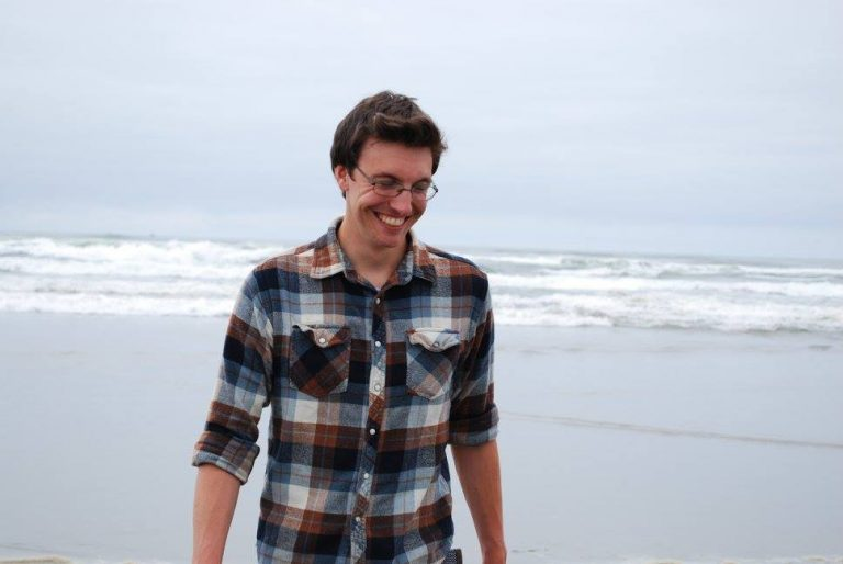 Arron Orr in a plaid shirt on the beach