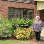 Sandy Newland stands outside The Cottage at WOU