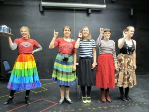 "Five women rehearsing for the play ""5 Lesbians Eating a Quiche,"" wearing colorful clothes."