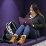 Female student using laptop in a purple-walled cubby.