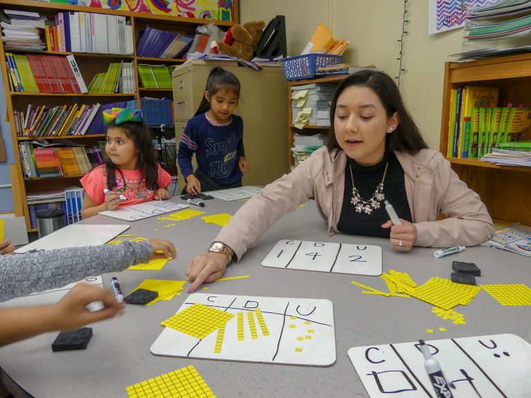 Jessica Zamarron helps students with a math assignment in a bilingual Swegle Elementary School classroom.