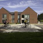 Two bicyclists riding in front of the Richard Woodcock Education Center