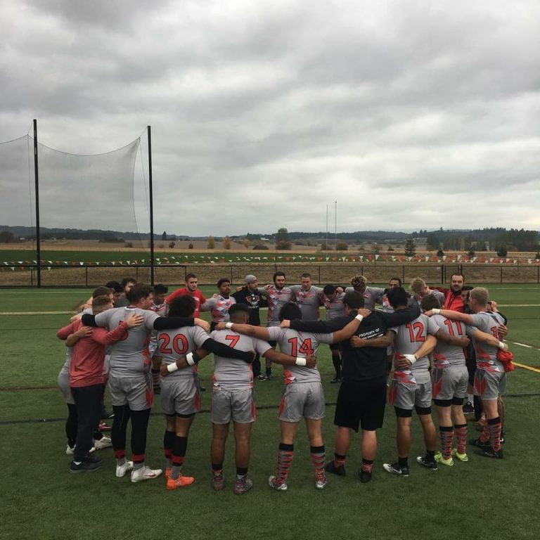 WOU men's rugby players huddling together