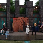 Several actors in costume of n an outdoor stage.