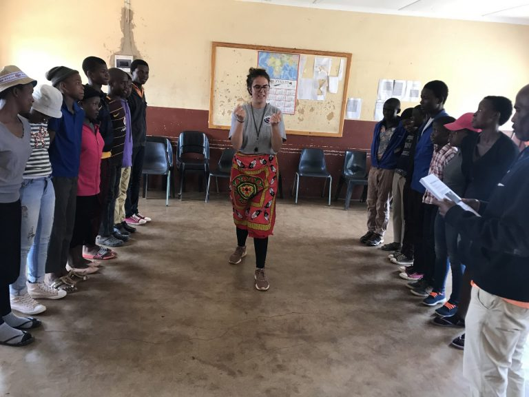 Amy Watkins standing in the middle of a group of people, teaching at Grassroots Soccer Camp in Eswatini.