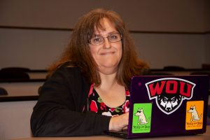 Person wearing a black jacket and glasses, sitting in front of an open laptop
