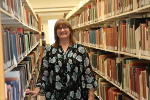 Chelle Batchelor standing and smiling between shelves of books in a library