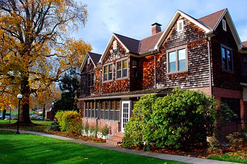 The Cottage, an older, rustic-looking building on the WOU campus. It is surrounded by green bushes and bathed in sunlight.
