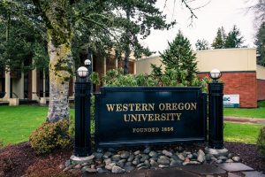 WOU sign at the front of campus, glossy black with gold lettering, greenery behind it. Campus appears wet from rain.