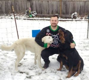 Man crouched down on snow petting two dogs