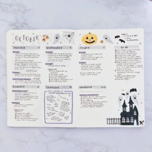 Filled bullet journal page decorated with a Halloween theme (bats, haunted house, jack-o-lantern, ghosts, and candy corn)