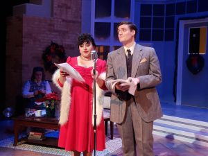 A woman in a red dress and a man in a suit stand behind a microphone on a stage