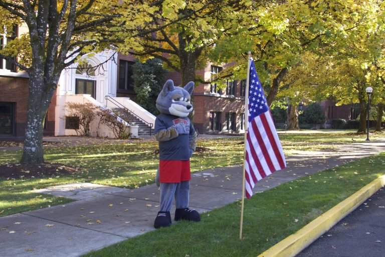 Wolfie with paw over his heart in front of an American flag outside our ITC building