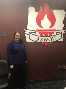 Felicia Dickinson stands in front of the ASWOU emblem in the WUC.