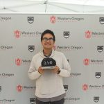 Person smiling as he stands in front of a layout of WOU logos. He is holding a hat with the symbols of his fraternity, shaded from the bright sun beyond him.