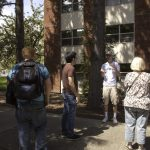 A WOU student leading a tour group on a sunny day