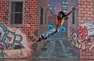 Man jumping in the air with arms spread wide in front of a background of brick walls and graffiti