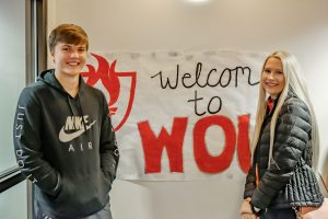 Two people stand next to a sign reading Welcome to WOU.