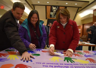Three people putting their handprints on a board.