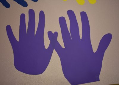 Two purple hands touching to form a W with their pinkies.