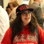 Student smiling and wearing WOU gear