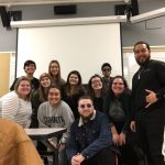 Eleven members of WOU's Acapella Club stand in front of a projector. They are all smiling.