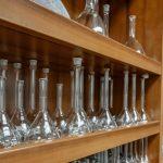 Glass beakers line a wood shelf.