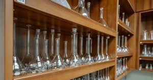 Glass beakers line a wood shelf.
