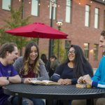 Group of four students sitting at a table outdoors and smiling