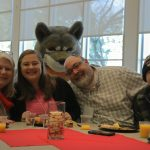 People sitting around the table enjoying a meal with Wolfie.
