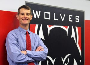 A person smiling next to the WOU logo.