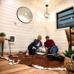 Two people sitting on the floor in the corner of a decorated room