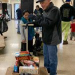Man standing next to a box of food