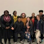 WOU's Black Student Union gathers for a picture. 10 individuals stand in front of a white board with smiles on their faces and arms wrapped around one another.