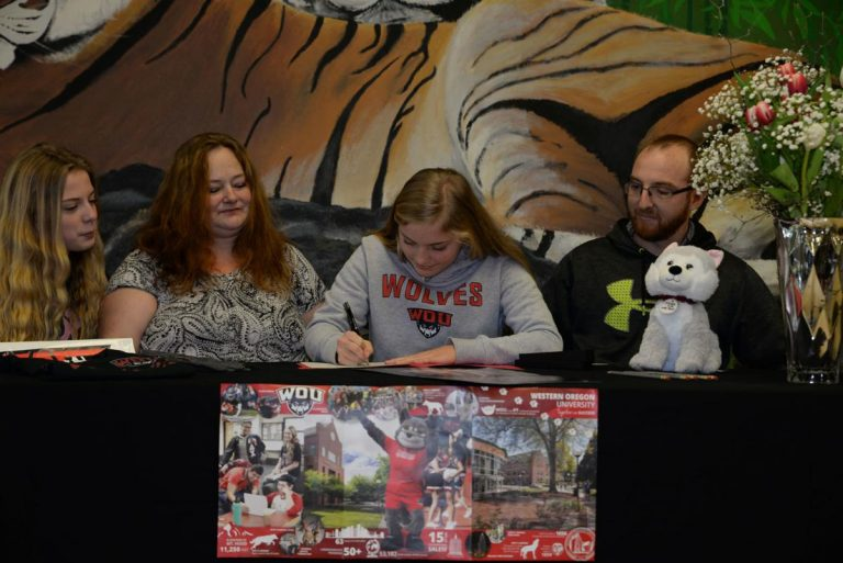 Student signing a document with family around her. She's wearing a Western sweatshirt