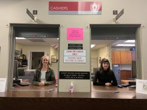 "WOU cashiers, Katie Rupp and Megan Blankenship pose in two cashier's windows. Above them is a sign which reads ""Cashiers."""