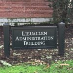 A sign in front of WOU's Lieuallen Administration Building. Behind the sign, which tells the name of the building, is a brick wall. Underneath the sign is bright green grass