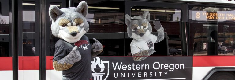 Wolfie standing by a bus.