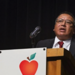 Man standing at podium and speaking